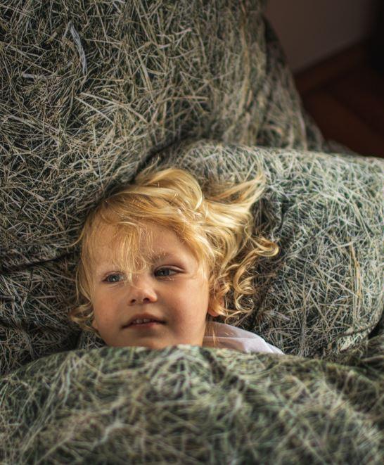 Chłopiec leżący w pościeli z nadrukiem siana
